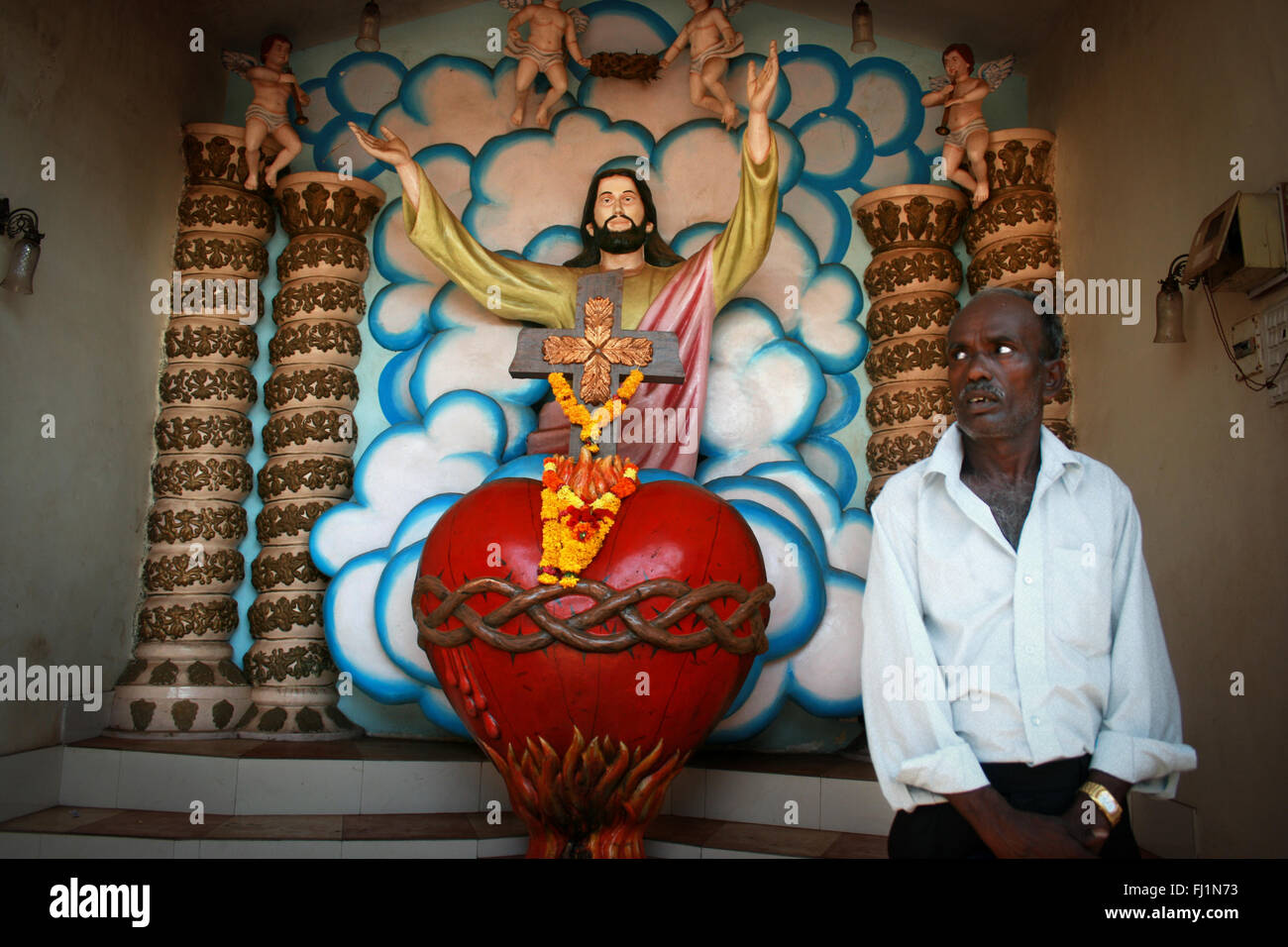 Indian catholic man inside Our Lady of Immaculate Conception Church witj colorful Jesus Christ statue, Panjim , - Stock Image