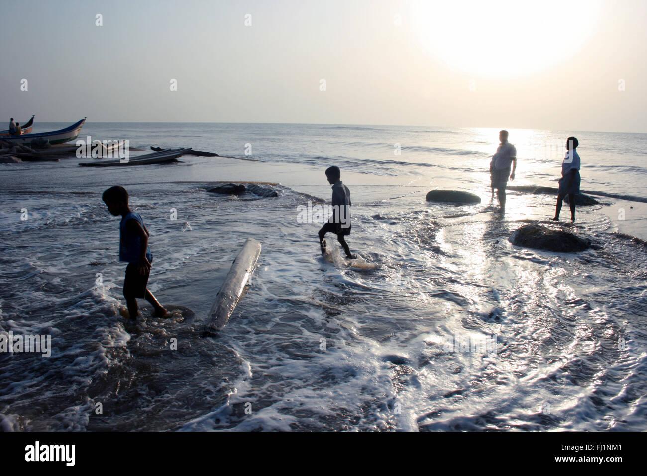 People walk by sunset on the beach in Puri, Orissa, India Stock Photo