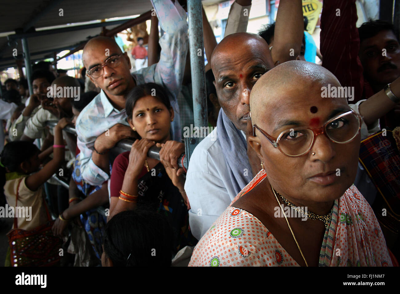 Hindu pilgrims queueing with their head shaved as offering made to god when visiting worldfamous pilgrimage place - Stock Image