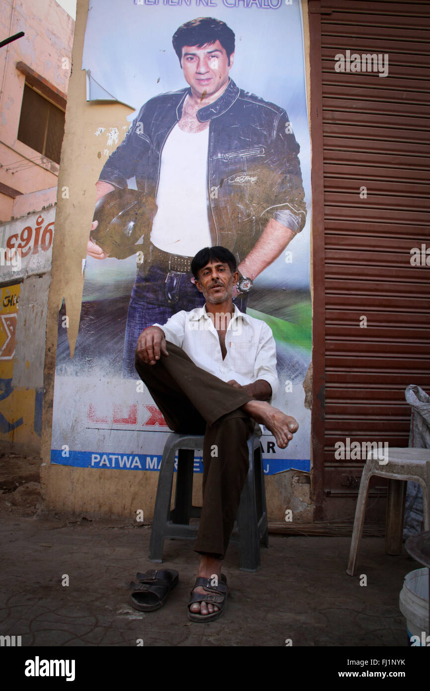 Man sitting alone in a street of Bhuj in front of Bollywood actor huge poster , Gujarat, India - Stock Image