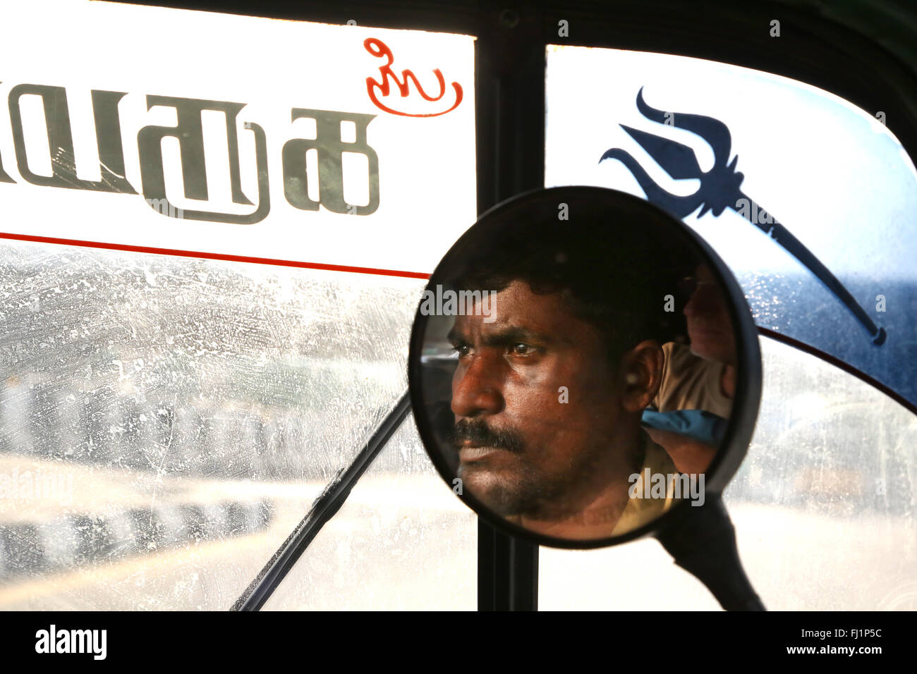 Close up on the face of a Rickshaw driver in mirror, Madurai , India - Stock Image