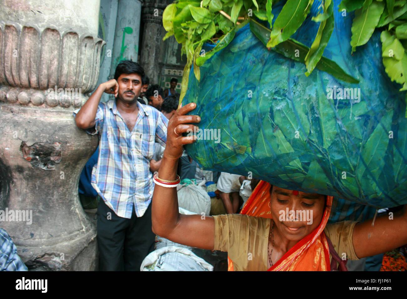 Woman carrying heavy bag - hard working at Kolkata flower market , India. A man is watching . - Stock Image