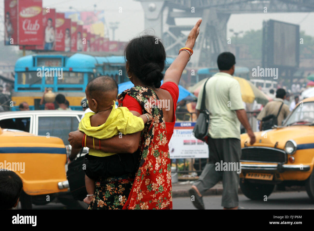 A woman carries her baby in the crowd at Howrah station in front of Howrah bridge , Kolkata , India Stock Photo
