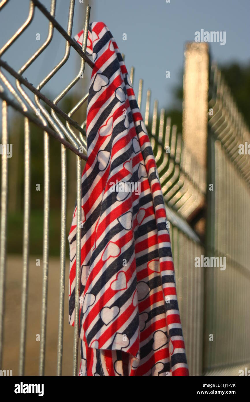 Welded wire fence with a piece of textile. - Stock Image