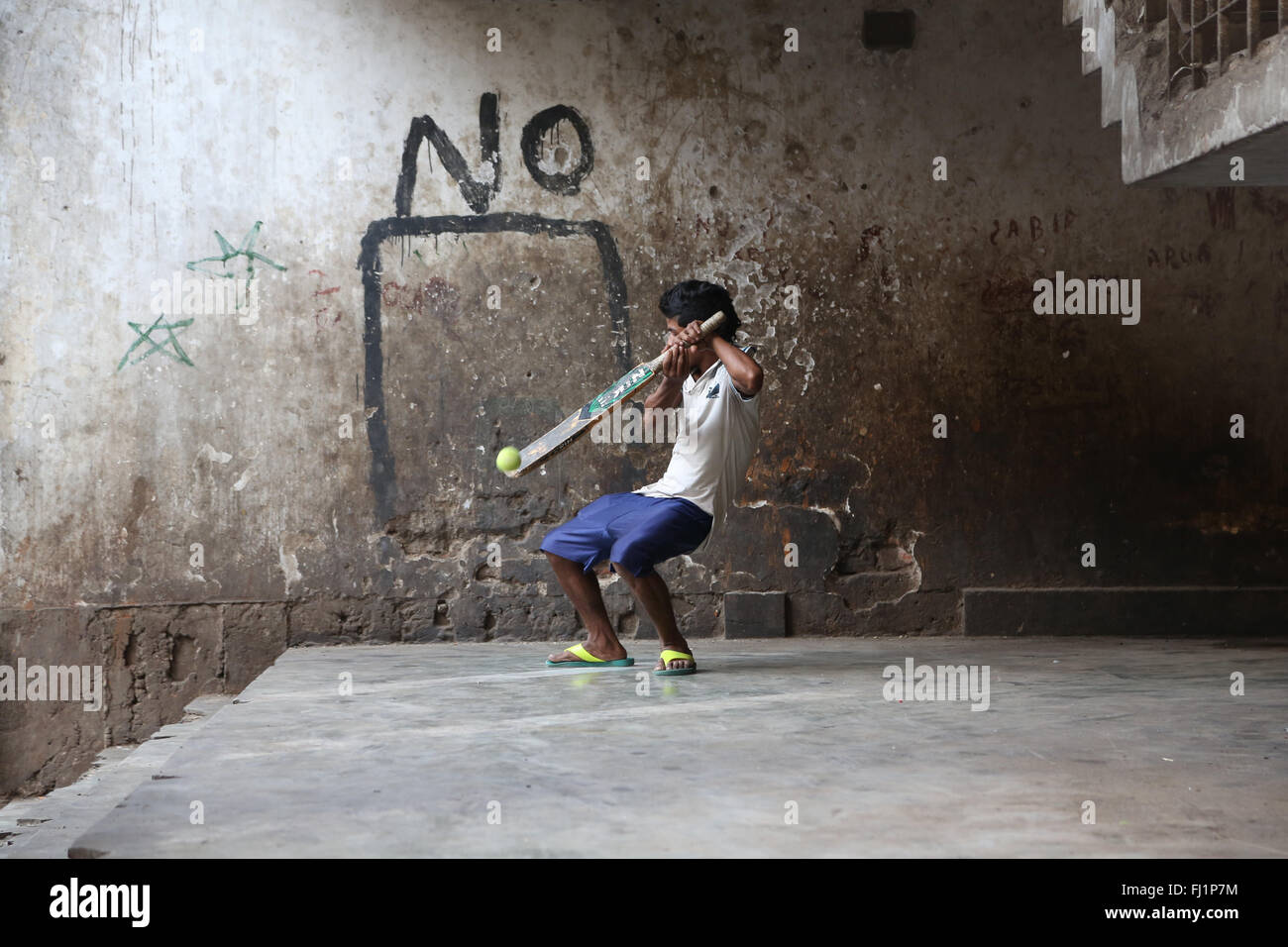 Young man playing cricket near New Market , Kolkata, with a 'No' writing on the wall behind him. He misses - Stock Image