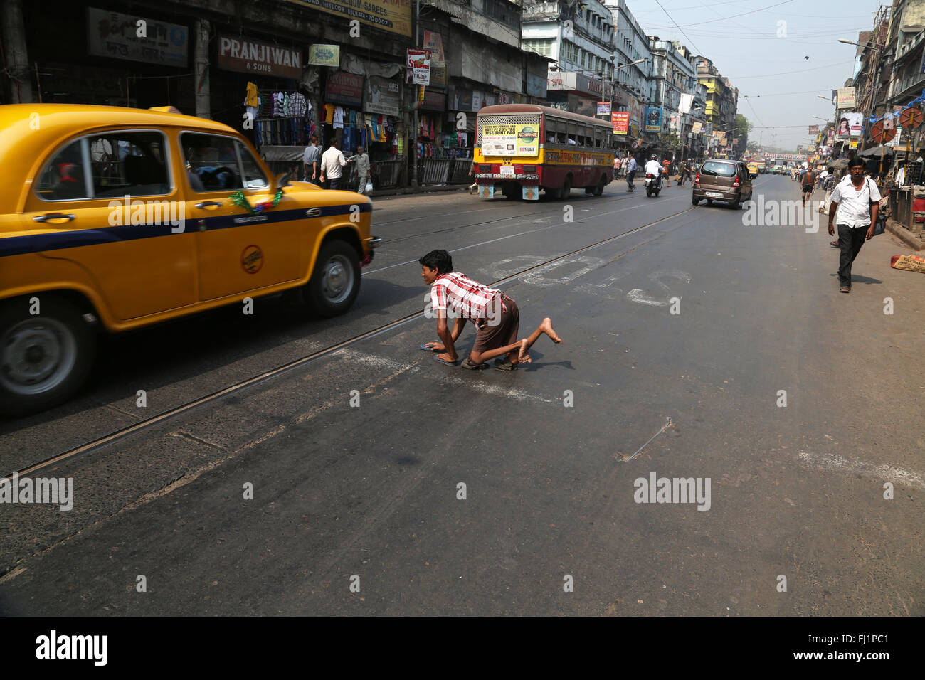 Disabled beggar man crosses a busy street in Kolkata , India - Stock Image