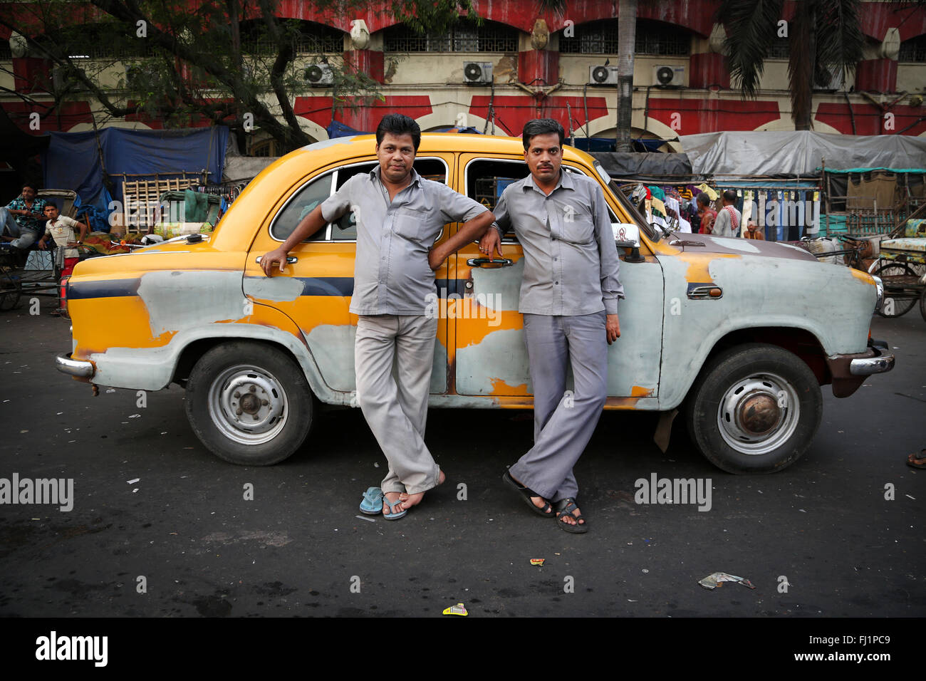 Two taxi cab drivers in  grey uniform are waiting for customers in front of classical yellow taxi at Howrah railway - Stock Image