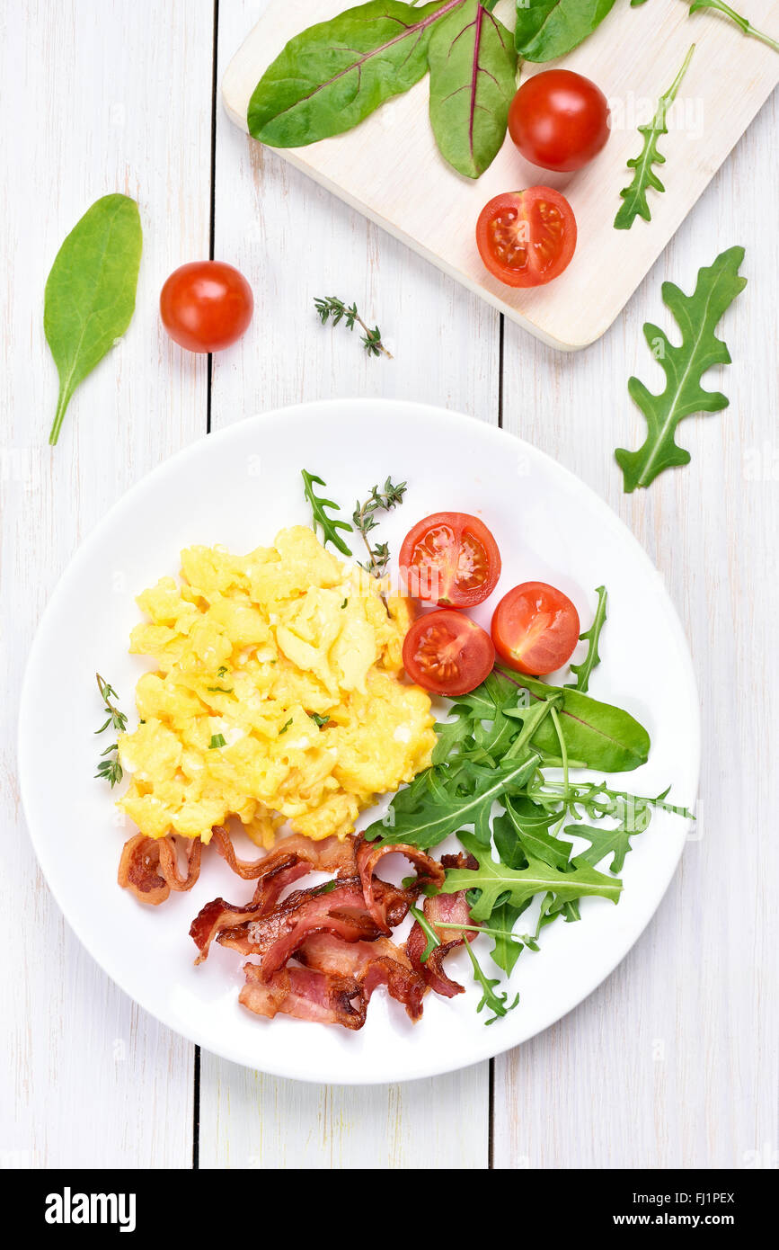 Breakfast with scrambled eggs, bacon and vegetable salad, top view - Stock Image