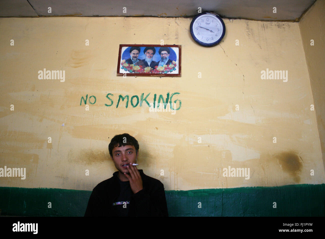 Kashmiri man smoking in restaurant in Leh, India, under a 'no smoking' writing on the wall - Stock Image