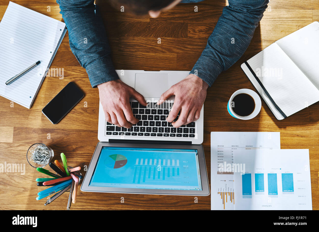 Top view working at desk with laptop and documents, business concept - Stock Image