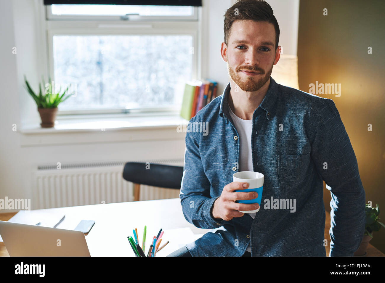 Confident young entrepreneur sitting in his office at the desk looking into the camera - Stock Image
