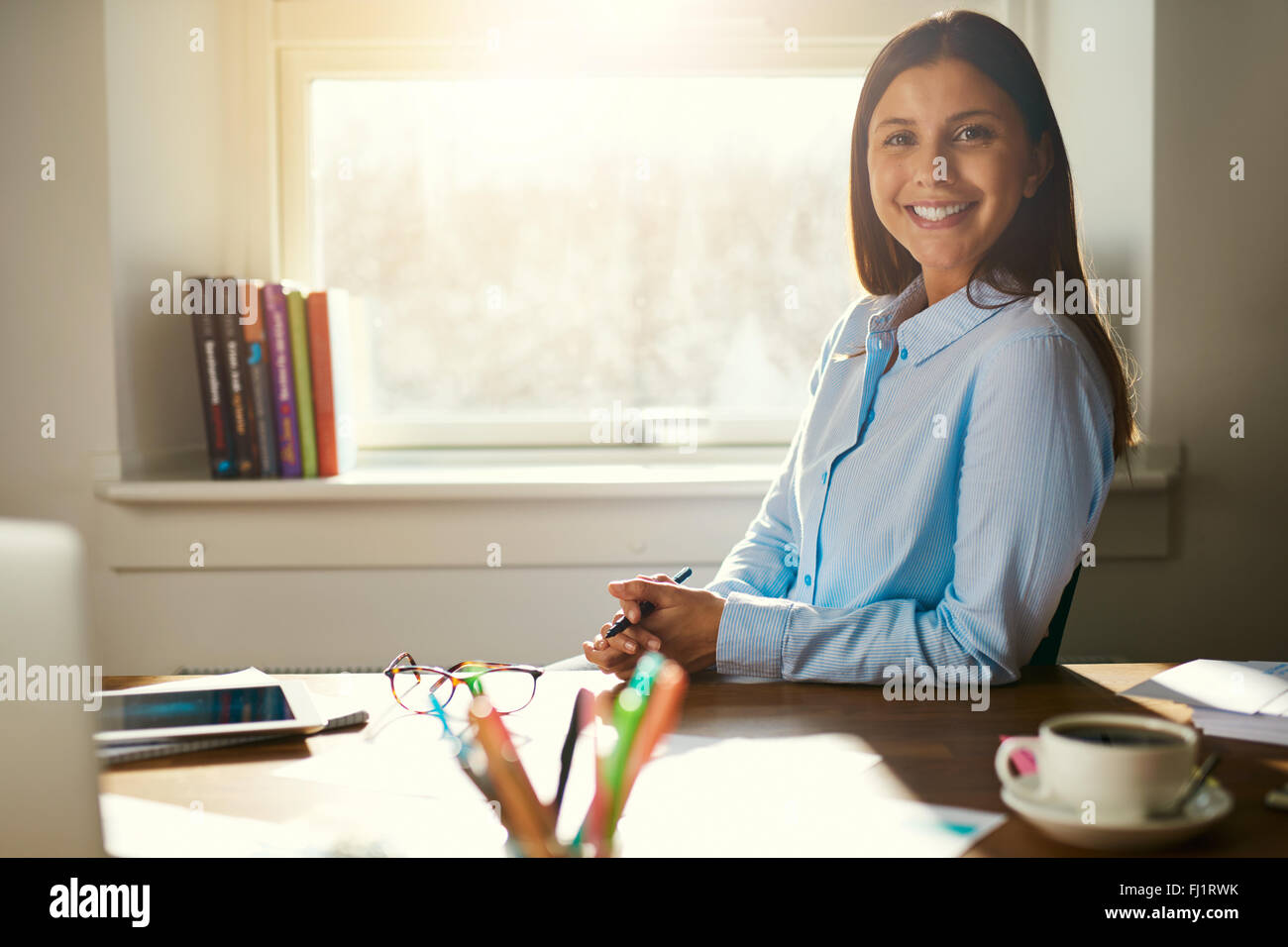 Successful business woman sitting at her desk in a office smiling at the camera - Stock Image