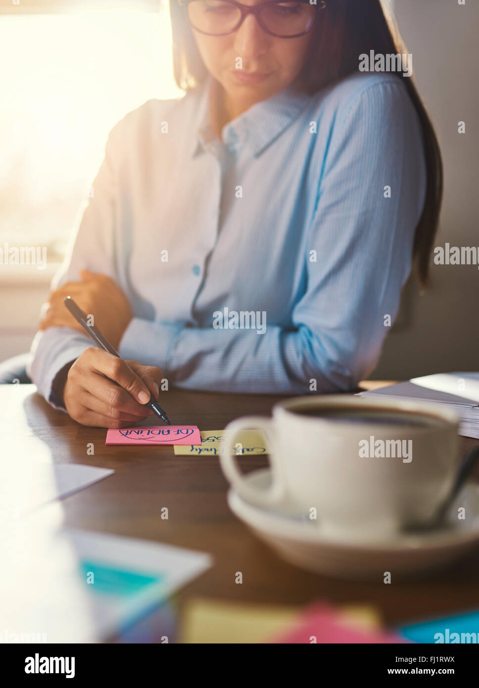 Female entrepreneur writing notes at desk, business woman look - Stock Image