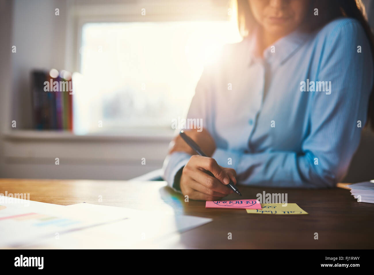 Closeup business woman writing notes on a post it - Stock Image