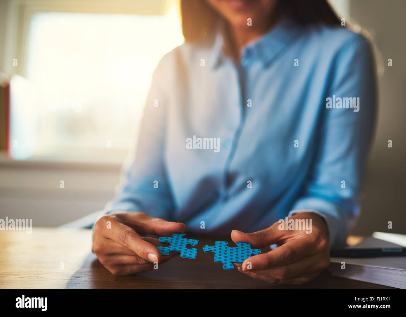 Business woman connecting puzzles, closeup of hands, success concept - Stock Image