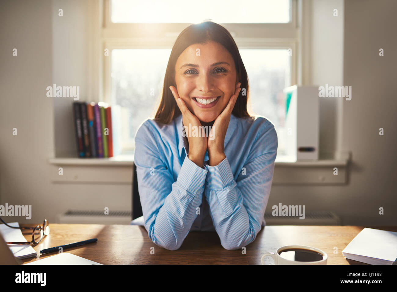 Female entrepreneur business woman smiling at camera working at office - Stock Image