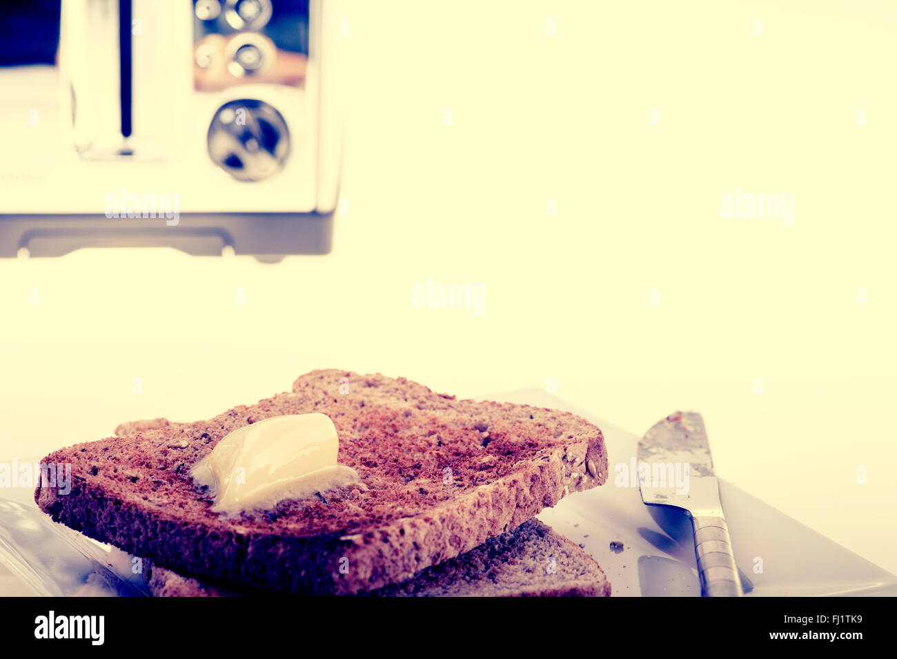 Two slices of toast and butter, with vintage cross process look. - Stock Image