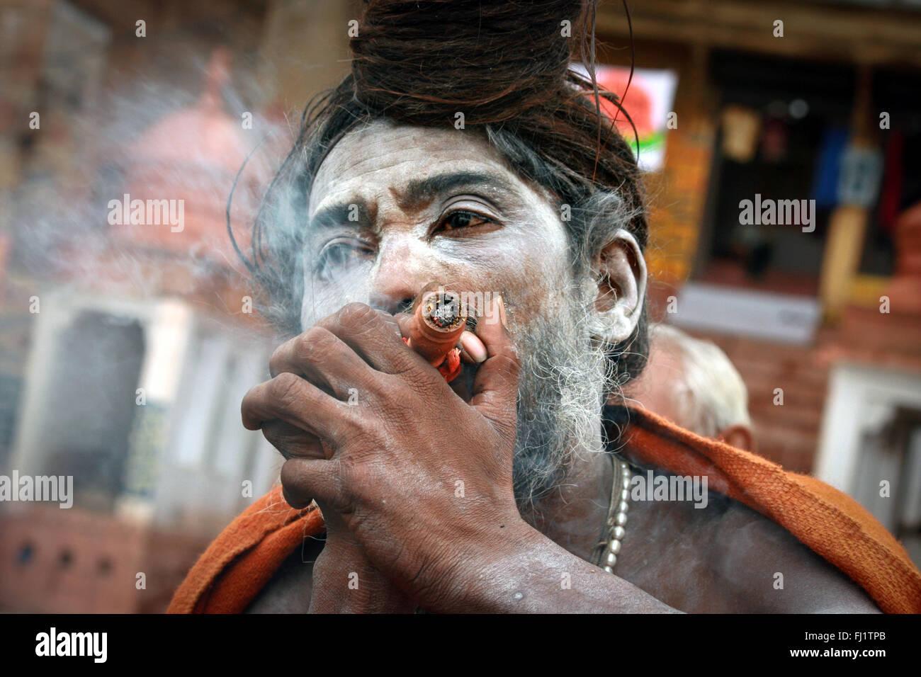 Sadhu holy man smoking chillum in  Varanasi, India - Stock Image