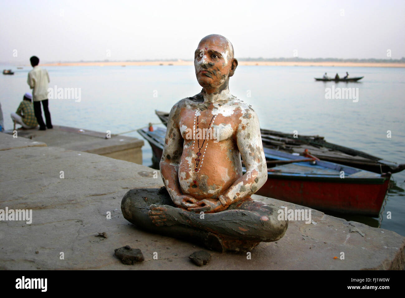 Old antique statue on the banks of the ganges , Varanasi, India - Architecture and daily street life - Stock Image