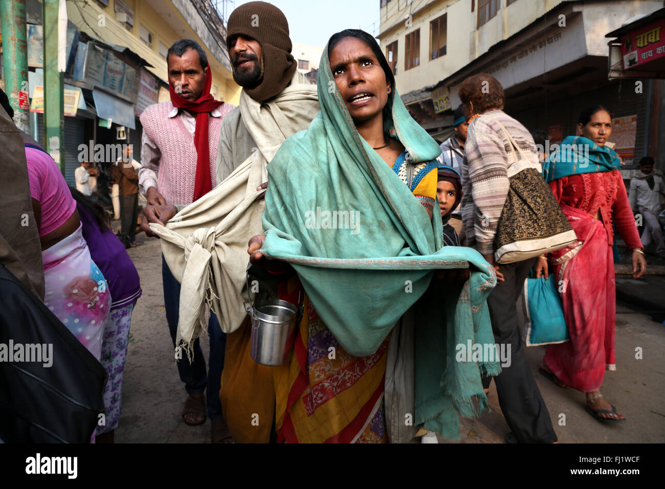 Indian woman begging beggar in the street in Varanasi, India - Stock Image