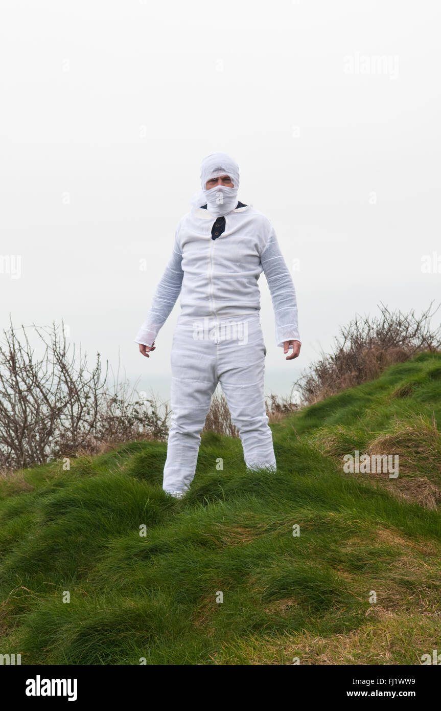 Man in a tight white boiler suit with his head in white bandages standing in a field - Stock Image