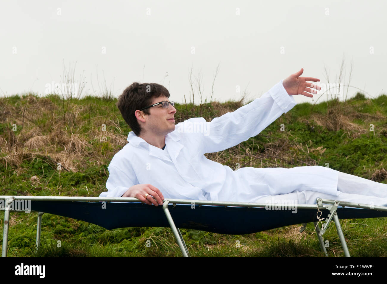 Man in a white doctor's or lab coat laying back on a blue camp bed waving his hand - Stock Image
