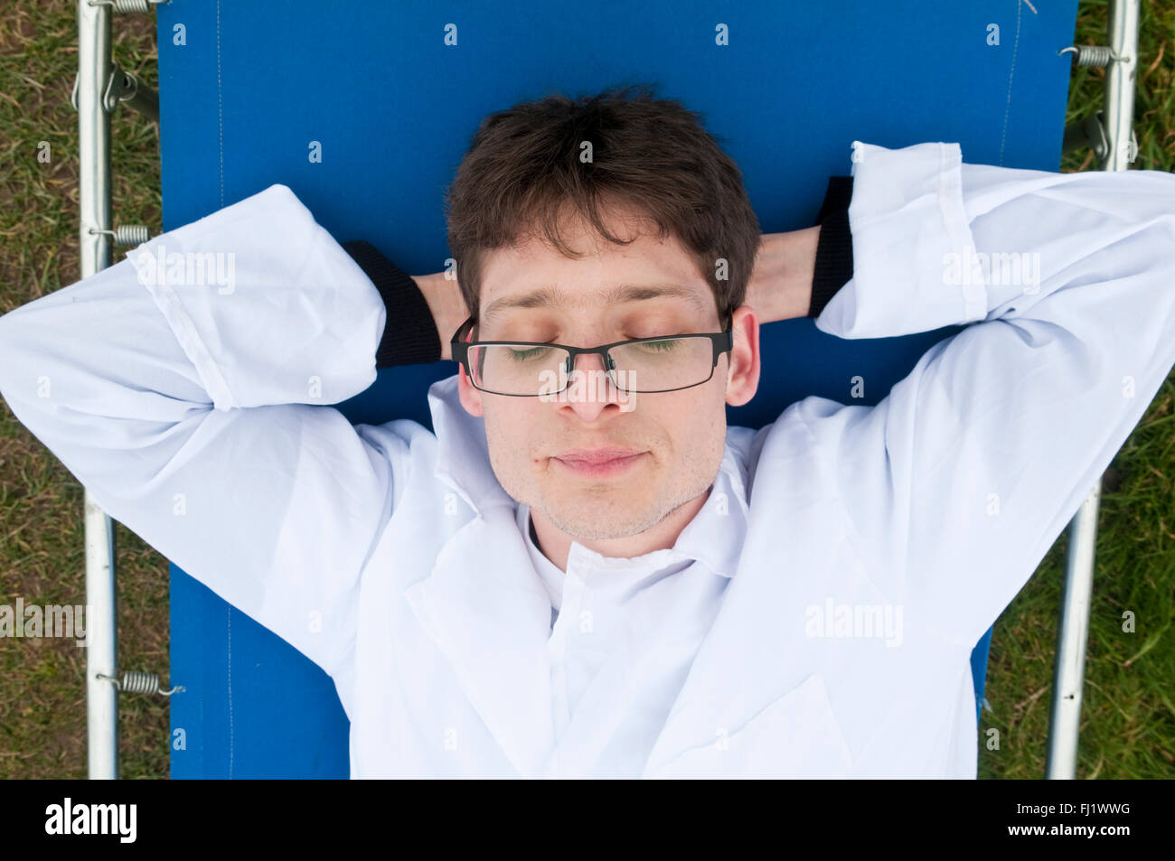 Man in a white doctor's or technician's lab coat laying back relaxing on a blue camp bed - Stock Image