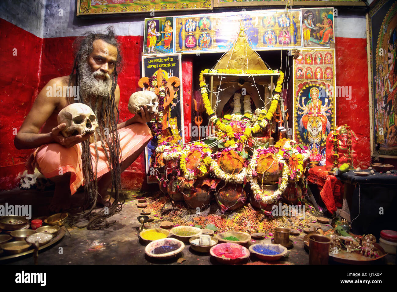 Portrait of Aghori cannibal sadhu holy man in front of decorated temple in Varanasi, India - Stock Image