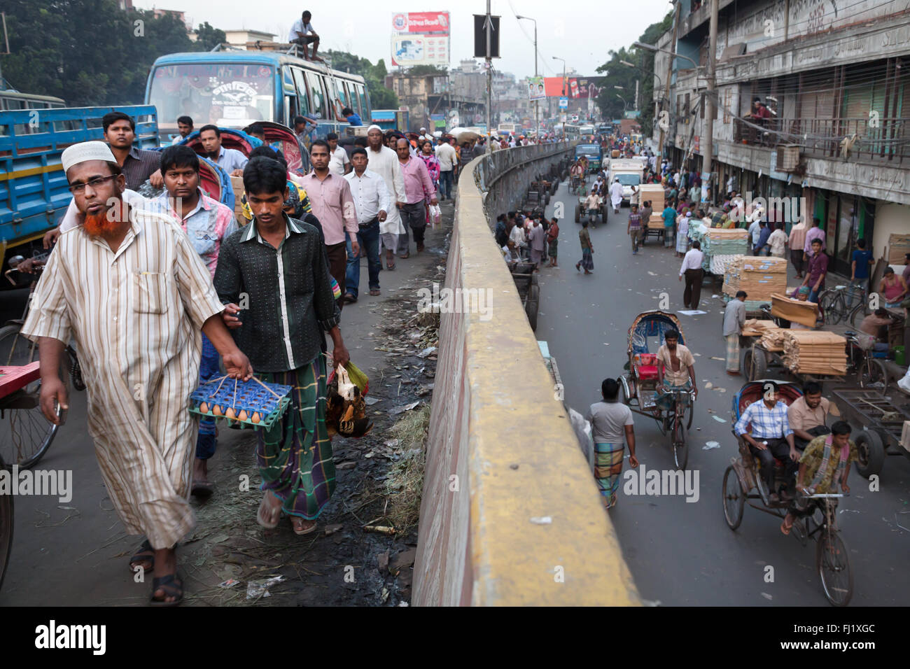 People walk in a crowded and busy street of Dhaka , Bangladesh  - landscape - Stock Image