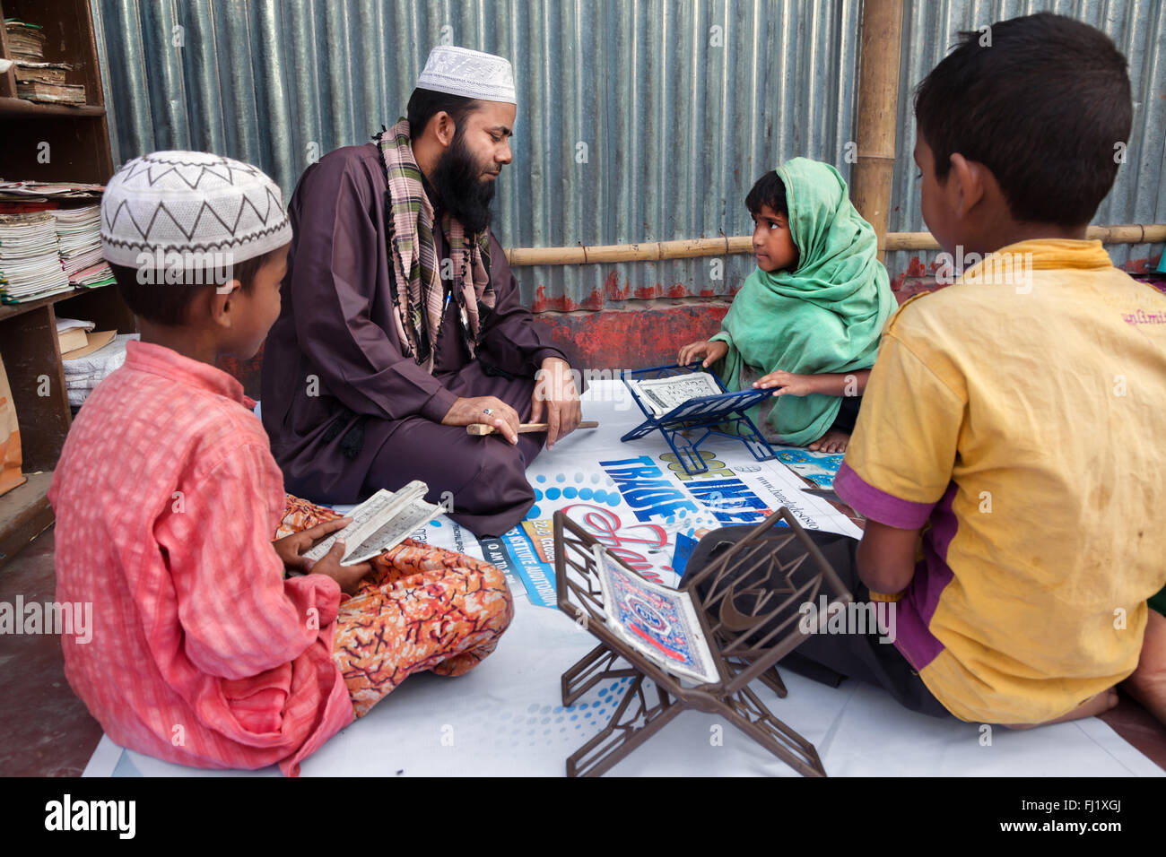 Coran teacher giving lessons in a slum in Dhaka , Bangladesh - Stock Image