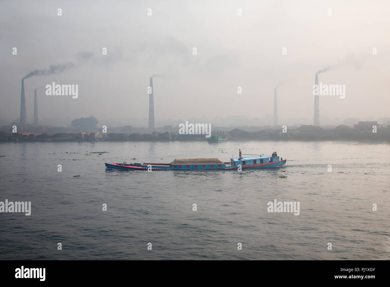 Buriganga river near Dhaka , Bangladesh , with brick factories at the back - Stock Image