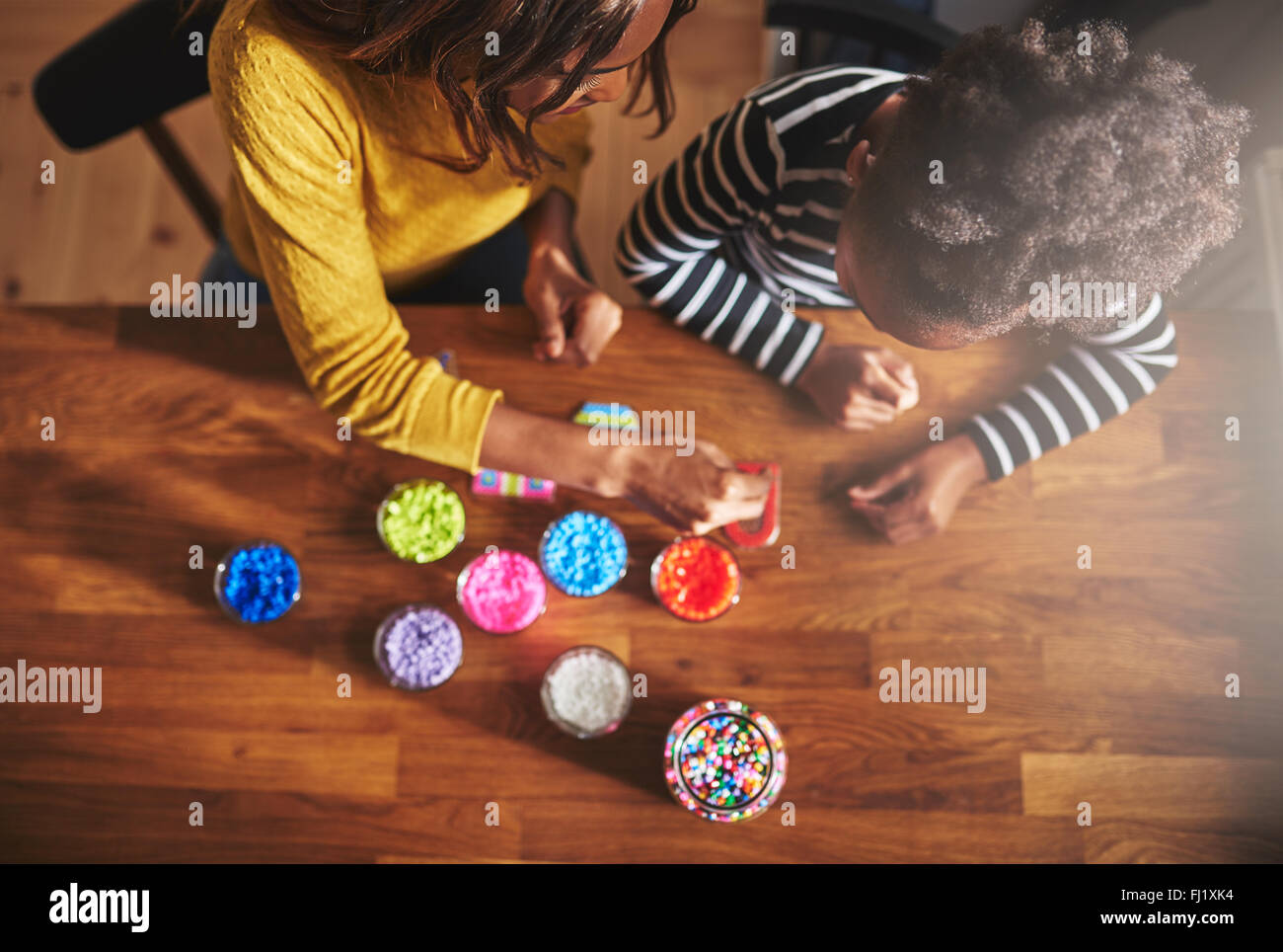 Top down view of seated adult and child choosing beads for crafting project on wooden table - Stock Image