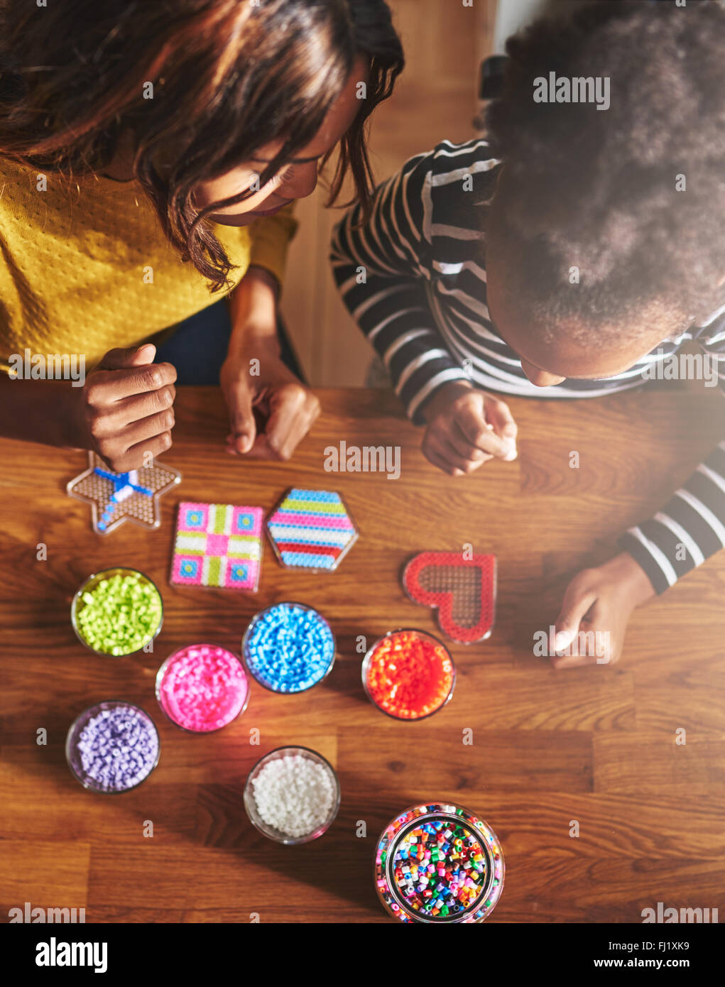 Top down view of seated adult and child finishing up their bead crafting project on wooden table with various jars - Stock Image