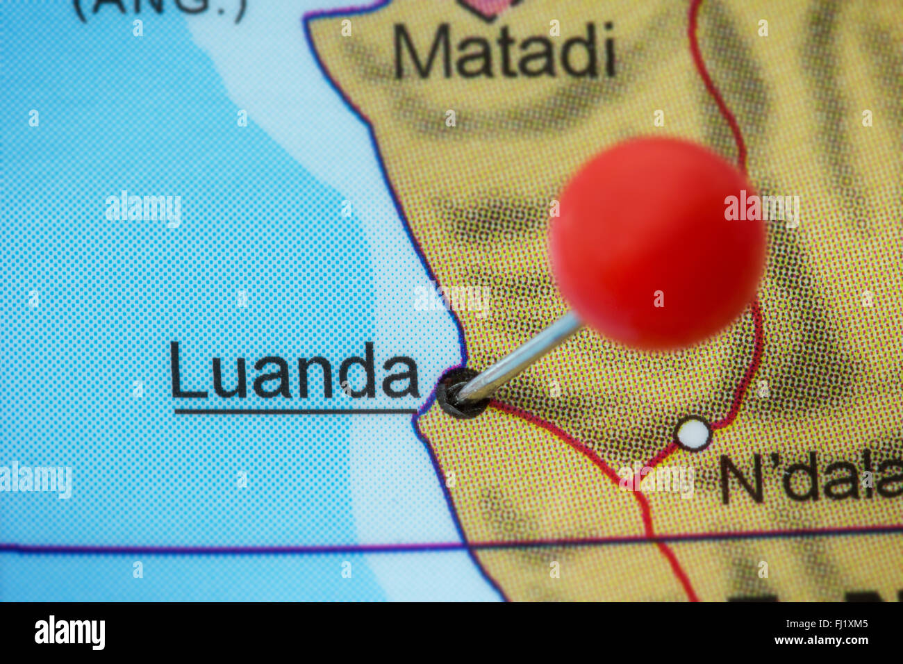 Close-up of a red pushpin in a map of Luanda, Angola. - Stock Image