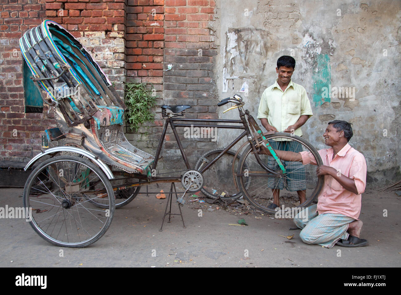 A smiling man repairs / changes a rickshaw flat tire with happy customer , Chittagong, Bangladesh - Stock Image