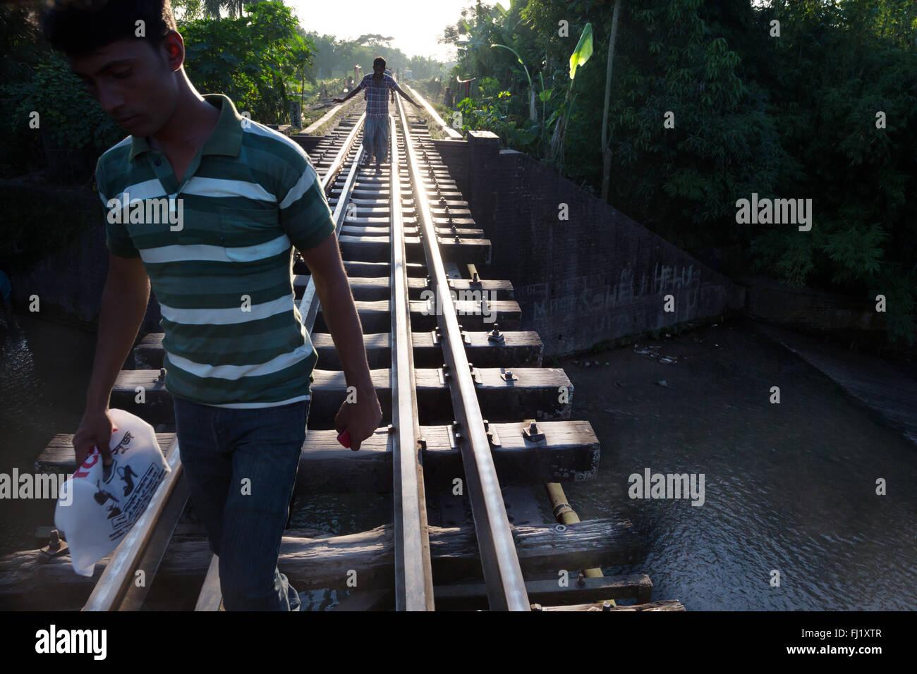 Men walk along train rails / tracks in Sreemangal , Bangladesh - Stock Image