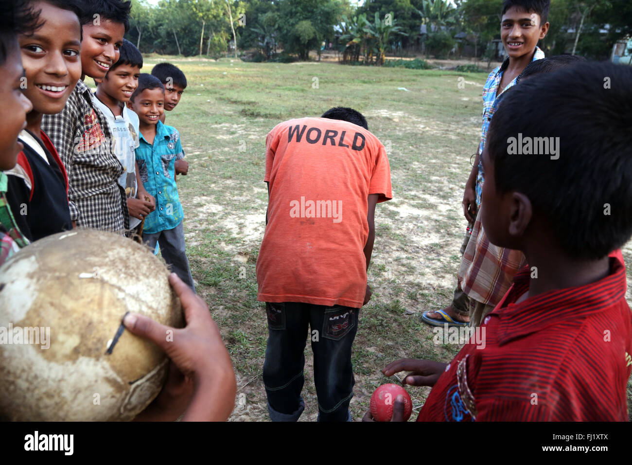 Happy smiling kids play football with 'WORLD' t shirt in Sreemangal , Bangladesh - Stock Image