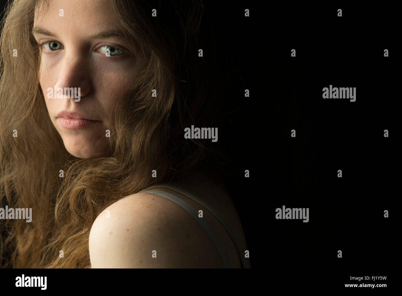 Beautiful young woman with fair skin and blue eyes and long brown hair, dramatically lit against a plain black background - Stock Image