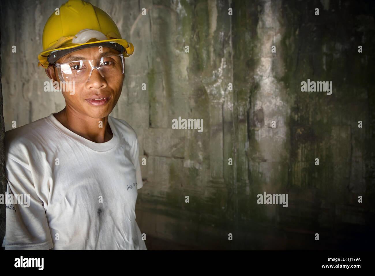Cambodian restoration worker inside  Angkor Vat - Stock Image