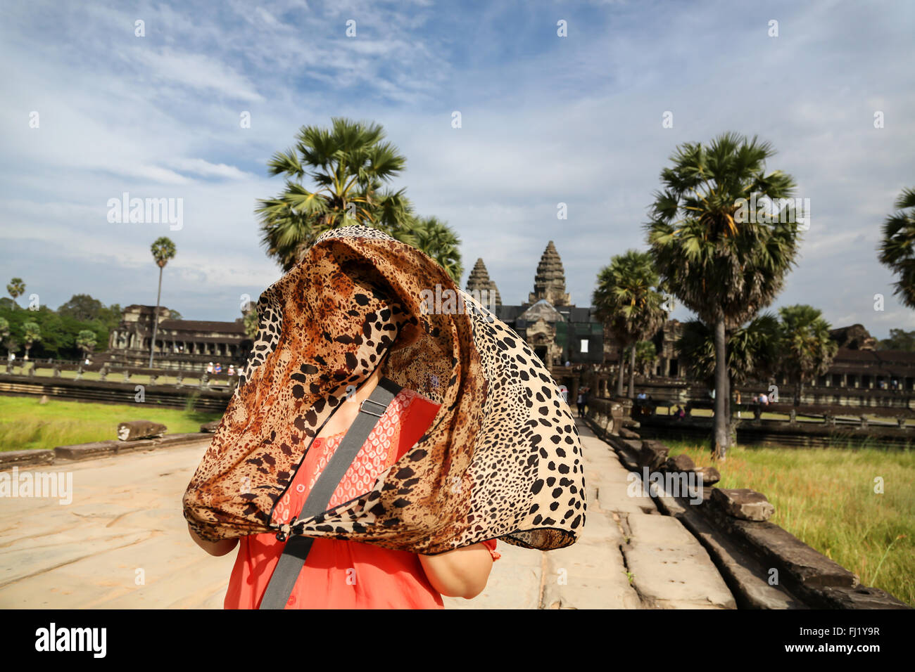 Tourist hidden under a jaguar pattern scarf in front of Angkor Vat, Cambodia - Stock Image