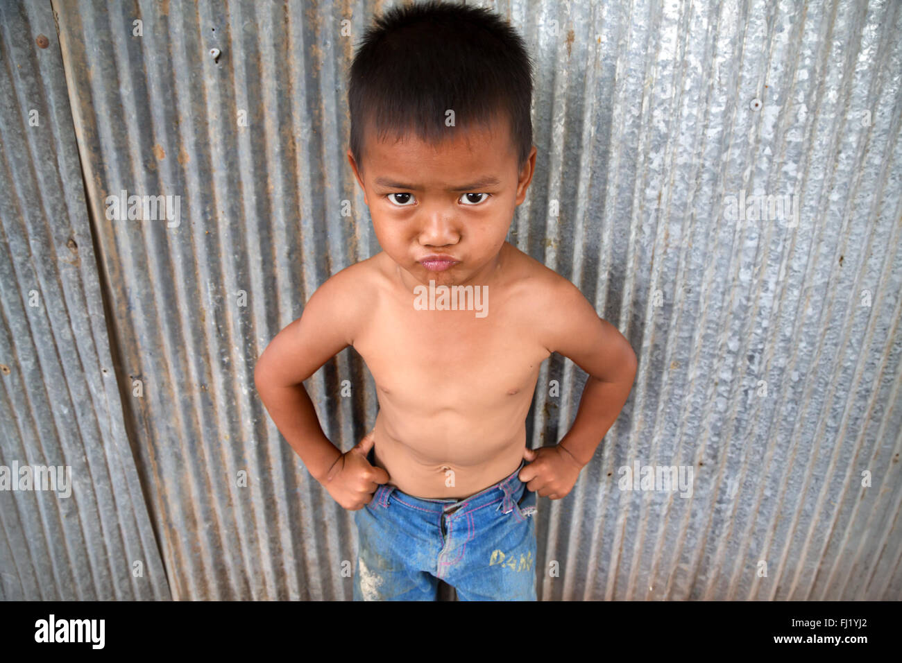Cute scowling kid in Kampot, Cambodia - Stock Image