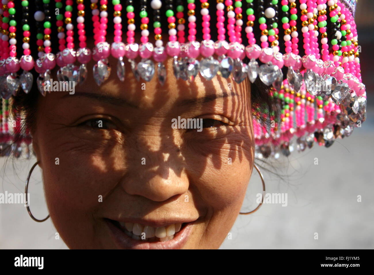 Tribal woman with traditional hat in Beijing, China - Stock Image
