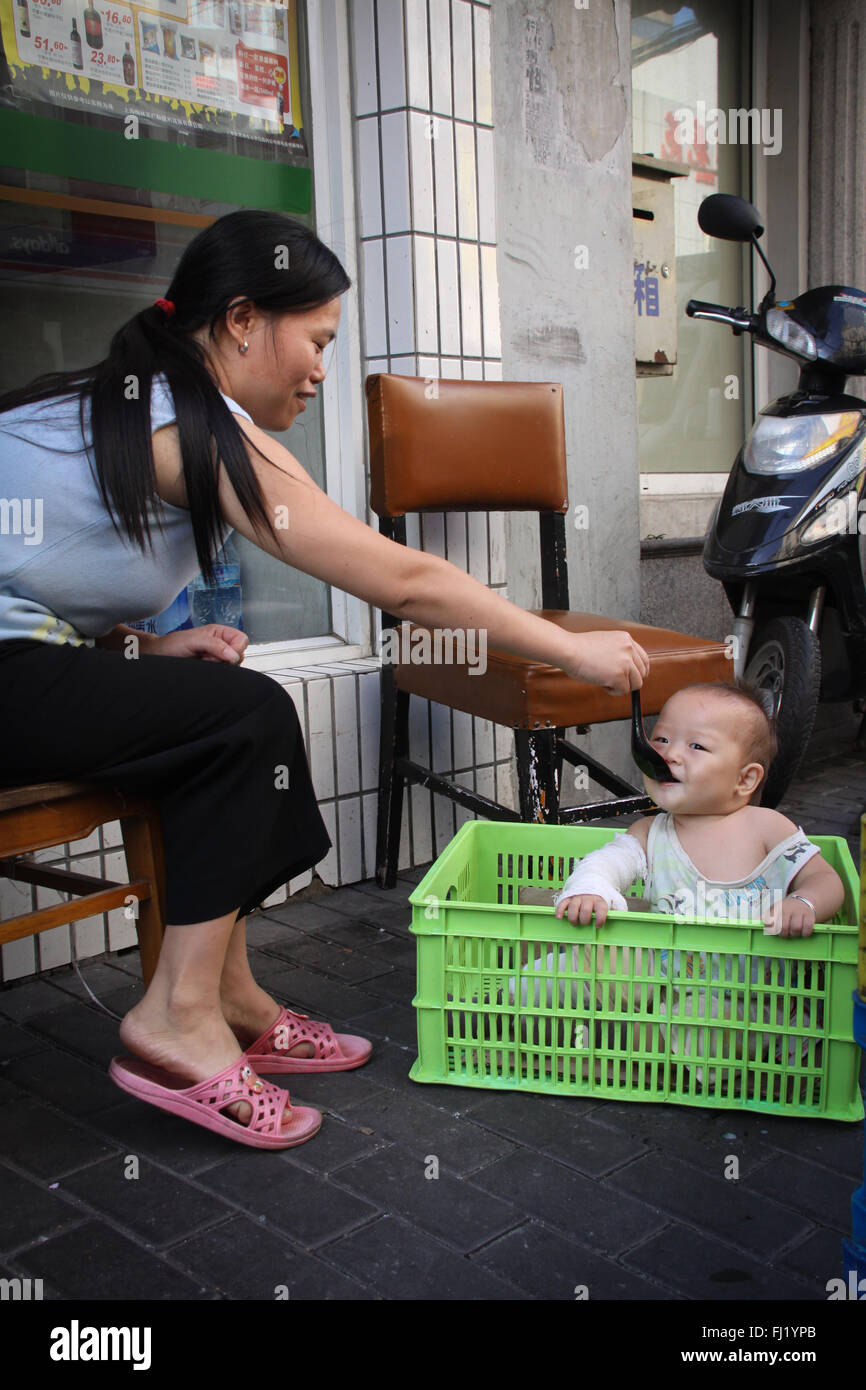 Mother feeding her baby in a street of Shanghai , China - Stock Image