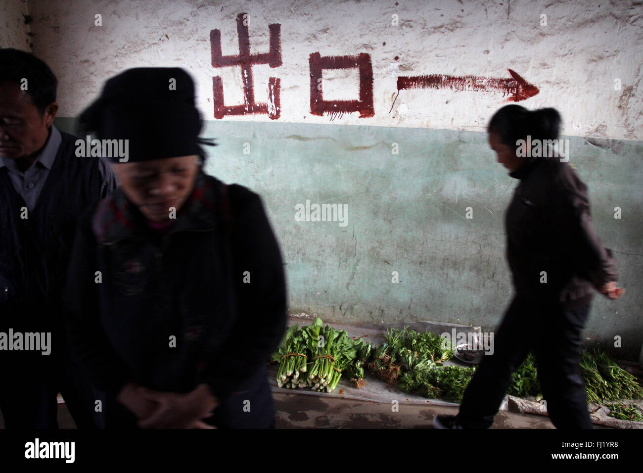 Women in Yuanyang market with arrow painted on a wall to show direction, Yuanyang, China - Stock Image
