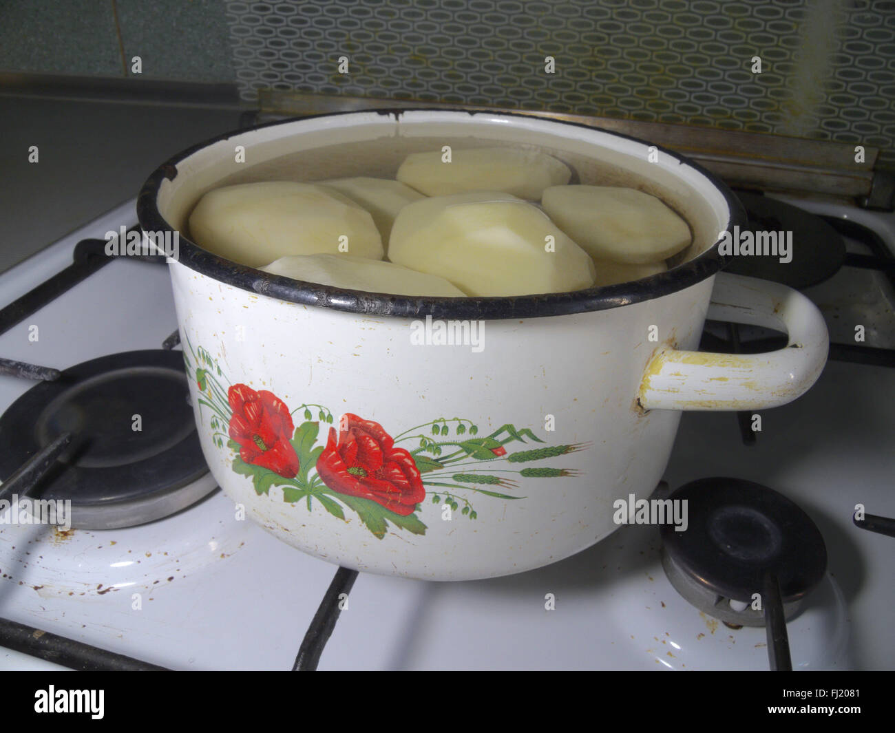 white pan with picture of vegetables, full of water and potatoes - Stock Image