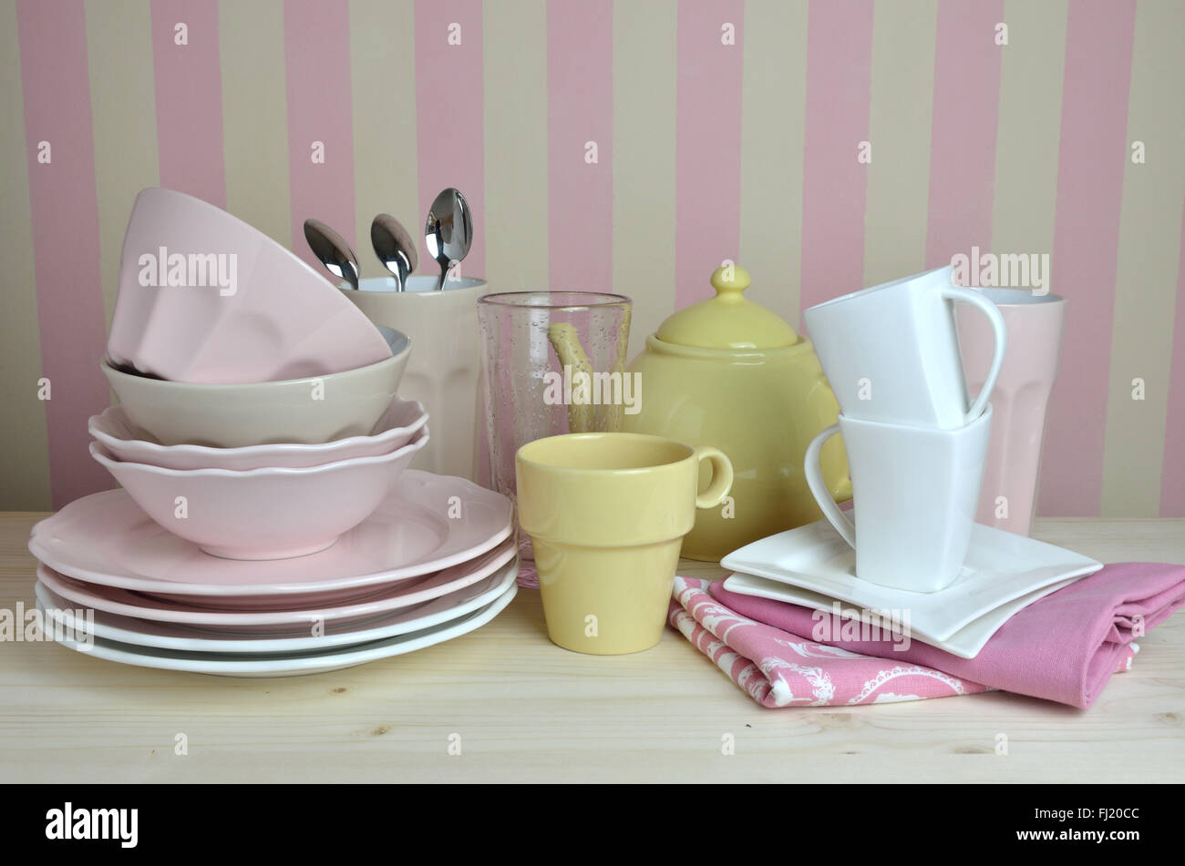 Crockery in pink, yellow and white color on kitchen desk with