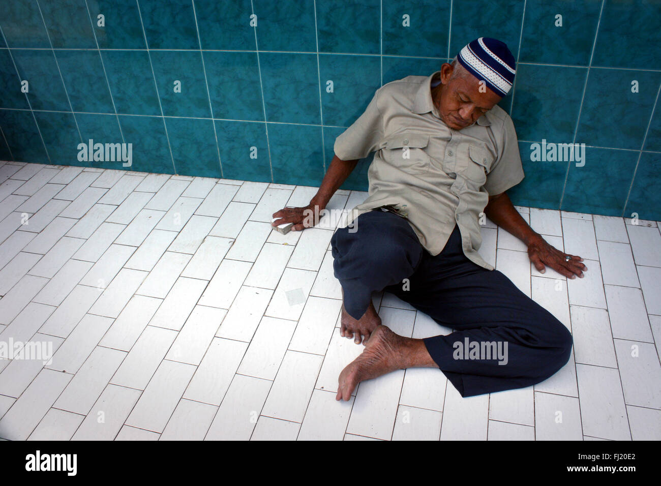 Muslim man sleeping in a mosque in Jakarta, Indonesia, during Ramadan - Stock Image