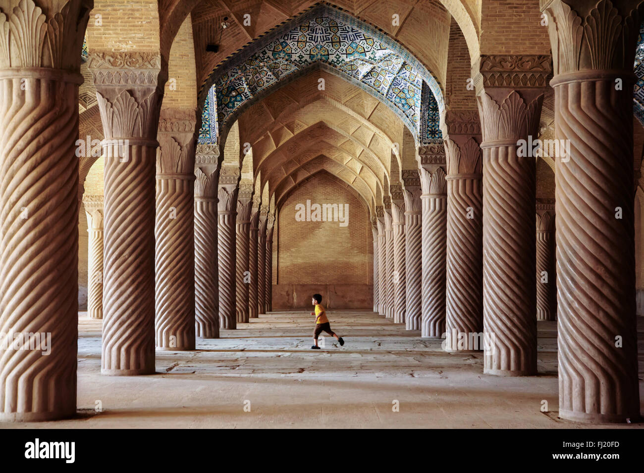 Child running inside Vakil mosque, Shiraz, Chiraz , Iran - Stock Image