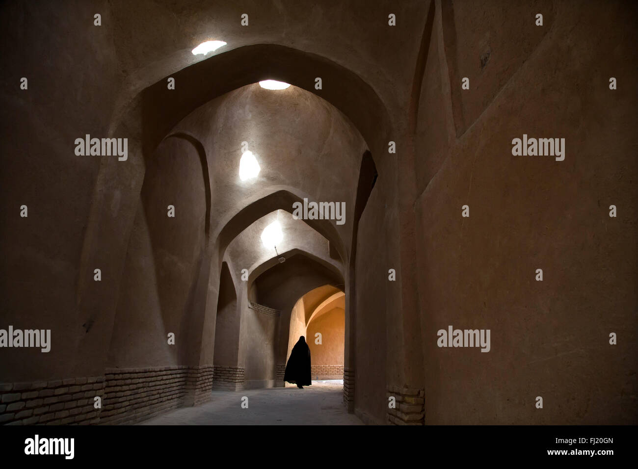 Veiled Iranian woman with niqab in the streets of Yazd, Iran - Stock Image