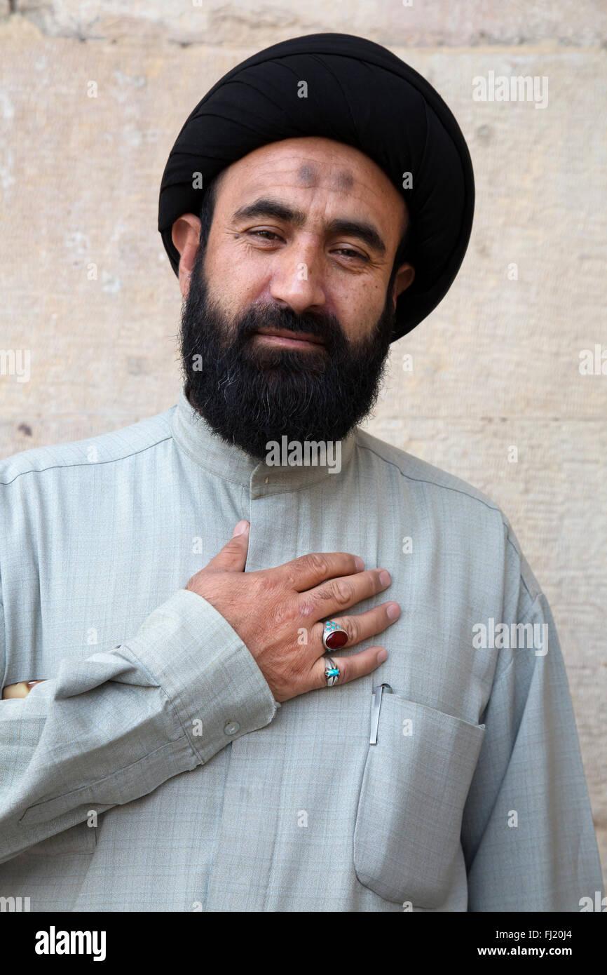 Portrait of Iranian religious man with Prayer bump and  hand on heart, Iran (Shia Islam) - Stock Image